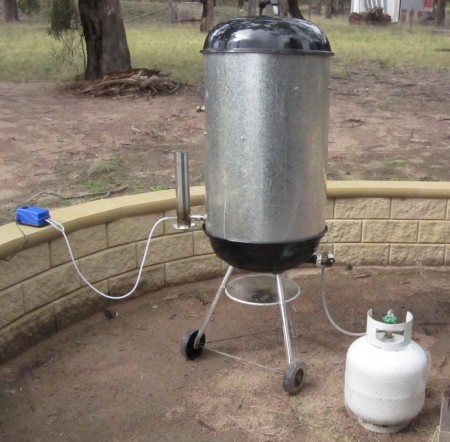 FrankenSmoker. A Converted Webber BBQ as a smoking vessel. The UFO Cold Smoke Generator is on the left. A small gas burner has been install at the bottom fed by a gas on the right.